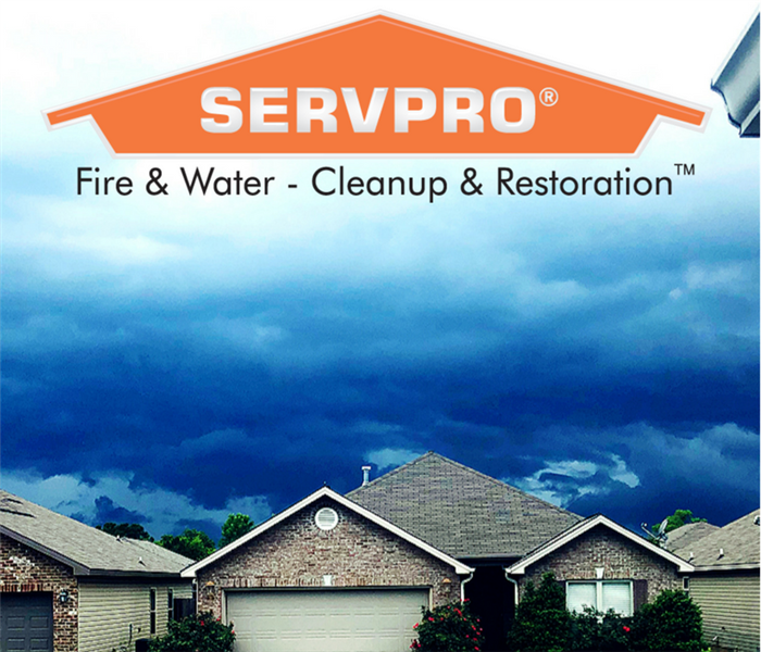 houses with dark skies overhead and SERVPRO logo at the top